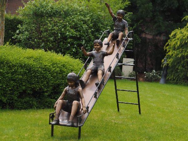 Bronzefigur 3 Kinder auf Rutsche