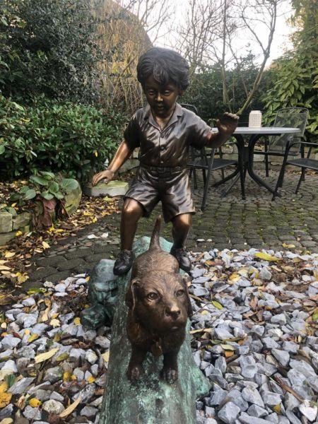 Bronzefigur Junge mit Hund auf Baumstamm