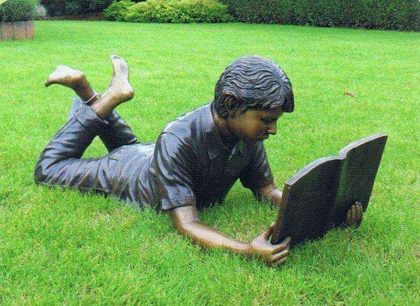 Bronzefigur Junge liegend lesend